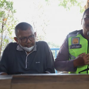 Bripka Eka Setiawan (tengah) berpelukan dengan pelaku di halaman Gedung Biru Polda Metro Jaya, Jakarta, Selasa (17/9).  [Suara.com/Angga Budhiyanto] - 3