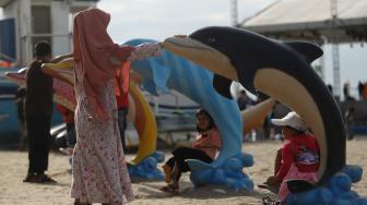 Pengunjung bermain di Pantai Langon, Ancol, Jakarta, Senin (25/12). [Suara.com/Muhaimin A Untung]
