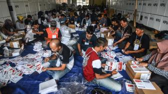 Sejumlah petugas melipat surat suara Pemilihan Presiden dan Wakil Presiden di Gudang Logistik KPU Kota Tasikmalaya, Jawa Barat, Senin (11/2). [ANTARA FOTO/Adeng Bustom]
