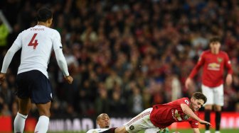 Gelandang Manchester United, Daniel James (kanan) dilanggar oleh pemain tengah Liverpool Fabinho selama selama pertandingan sepak bola Liga Inggris antara Manchester United melawan Liverpool di Old Trafford, Manchester, Inggris, Senin (21/10). dini hari WIB. [Oli SCARFF / AFP]