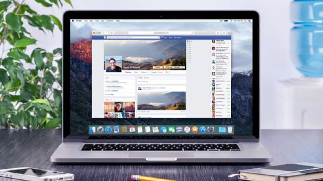 Facebook Timeline in user profile on the Apple Macbook Pro Retina screen that is on office wooden desk. Facebook is the most popular social network in the world. Varna, Bulgaria - May 31, 2015.