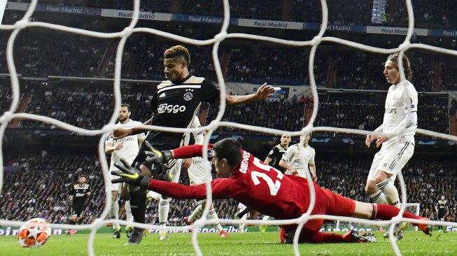 Pemain depan Ajax David Neres mencetak gol setelah melewati kiper Real Madrid Thibaut Courtois pada pertandingan leg kedua babak 16 besar Liga Champions antara Real Madrid melawan Ajax Amsterdam di Stadion Santiago Bernabeu, Madrid, Rabu (6/3) dini hari WIB. [JAVIER SORIANO / AFP]