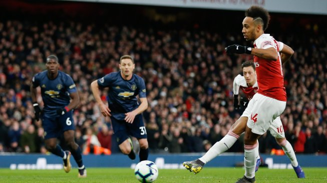 Striker Arsenal Aubameyang mencetak gol kedua dari titik penalti selama pertandingan sepak bola Liga Primer Inggris antara Arsenal melawan Manchester United di Stadion Emirates, London, Inggris, Minggu (10/3). [Ian KINGTON / IKIMAGES / AFP]