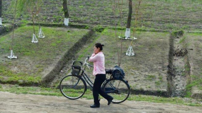 Seorang perempuan di Korea Utara sedang menuntun sepeda sembari berbicara di ponsel. [Shutterstock]