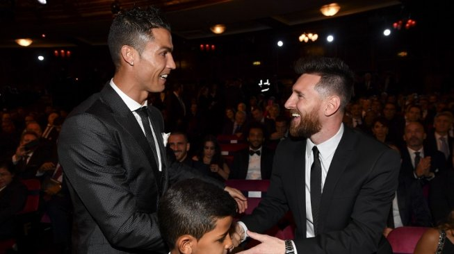 Cristiano Ronaldo (kiri) menajabat tangan Lionel Messi pada seremoni The Best FIFA Football Awards 2017 di London. [Ben STANSALL / AFP]