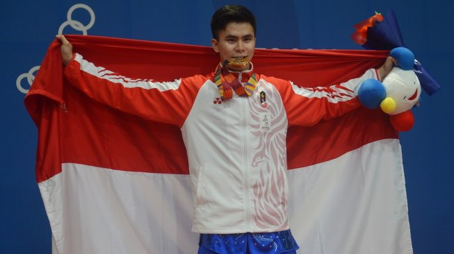 Atlet wushu Indonesia Edgar Xavier Marvelo menggigit medali setelah memenangi nomor gunshu putra SEA Games 2019 di gedung World Trade Center Manila, Filipina, Selasa (3/12). [Antara/Nyoman Budhiana]