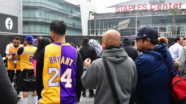 Penggemar Kobe Bryant berduka saat berkumpul di depan Staples Center, Los Angeles Lakers, Amerika, Minggu (26/1). [Frederic J. Brown / AFP]