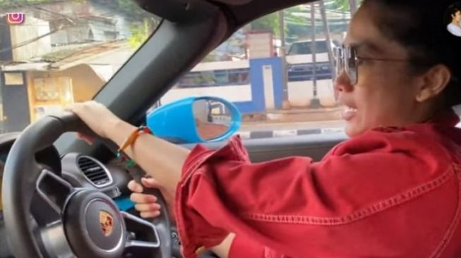 Ussy Sulistiawaty mengemudikan Porsche Boxter [scrrenshot: YouTube Ussy Andhika Official].