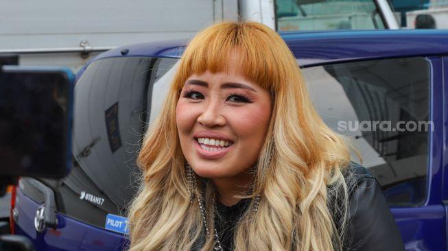 La cantante Pinkan Mambo mientras responde a las preguntas de los equipos de los medios de comunicación en el área de Tendean, en el sur de Yakarta, el viernes (9/11). [Suara.com/Alfian Winanto]
