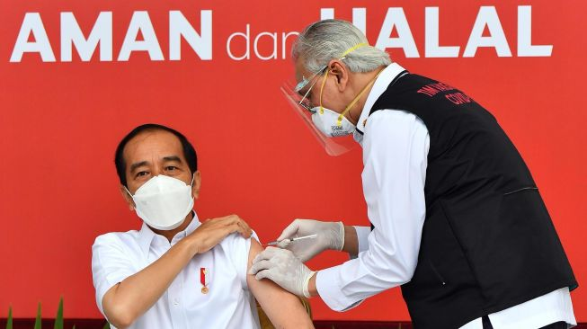 President Joko Widodo (center) prepares to be injected with the first dose of the COVID-19 vaccine produced by Sinovac by the vaccinator Deputy Chief Medical Officer Prof. Abdul Mutalib (right) on the veranda of the Merdeka Palace, Jakarta, Wednesday (13/1/2021). [ANTARA FOTO/HO/Setpres-Agus Suparto]