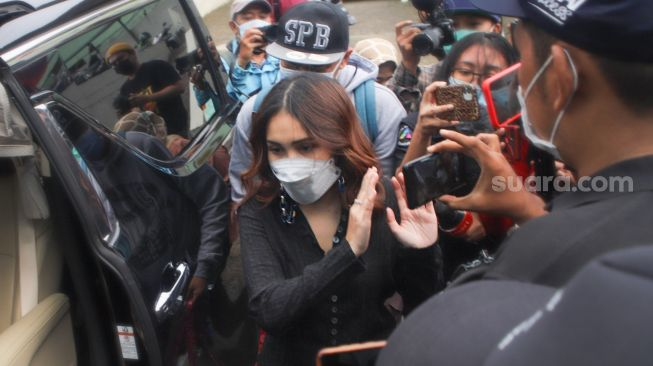 Sworddut Ayu Ting Ting walked to avoid media crews when met in the Tendean area, South Jakarta, Wednesday (27/1/2021). [Suara.com/Alfian Winanto]