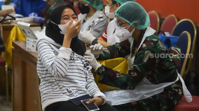 The expression of a resident while undergoing a Covid-19 vaccination at the Ciracas Sports Center, East Jakarta, Friday (2/7/2021). [Suara.com/Alfian Winanto]