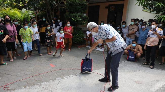 Gubernur Jawa Tengah Ganjar Pranowo dan Wali Kota Solo Gibran Rakabuming Raka saat mengunjungi pasien Covid-19 yang diIsolasi di SD Cemara Solo. [Dok Pemprov Jateng]