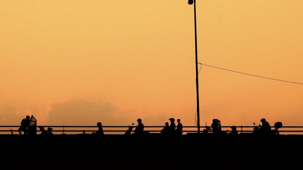 Sejumlah warga menunggu waktu berbuka puasa di Fly Over Pasar Rebo, Kamis (16/5). [Suara.com/Muhaimin A Untung]