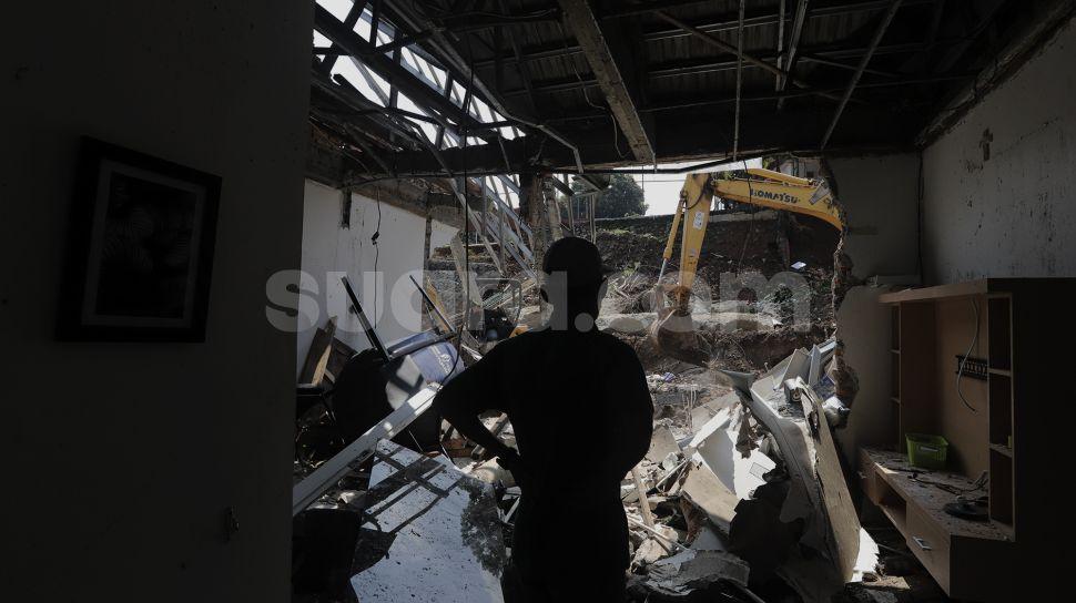 Warga melihat rumah yang hancur tertimpa tanah longsor di Perumahan Nerada Estate Ciputat, Tangerang Selatan, Banten, Sabtu (12/6/2021). [Suara.com/Angga Budhiyanto]