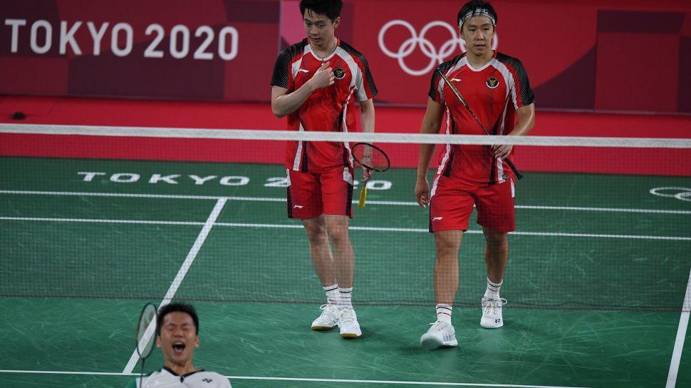 Ganda putra Indonesia Marcus Fernaldi Gideon (kanan) dan Kevin Sanjaya Sukamuljo (kedua kanan) berjalan seusai kalah dari ganda putra Taiwan Yang Lee/Chi-Lin Wang dalam penyisihan Grup A Olimpiade Tokyo 2020 di Musashino Forest Sport Plaza, Tokyo, Jepang, Selasa (27/7/2021).  ANTARA FOTO/Sigid Kurniawan