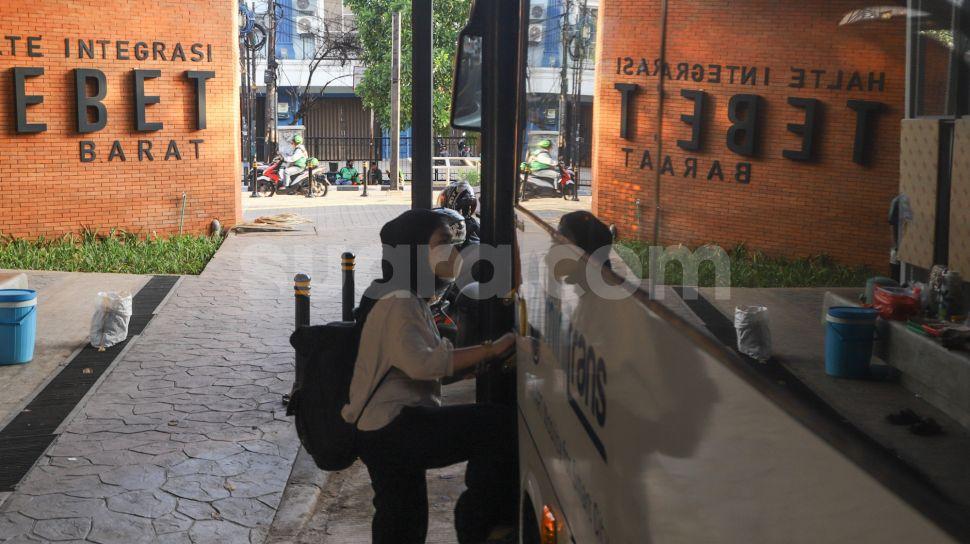 Penumpang menaiki bus Transjakarta di halte integrasi sisi barat Stasiun Tebet, Jakarta Selatan, Kamis (16/9/2021). [Suara.com/Alfian Winanto]