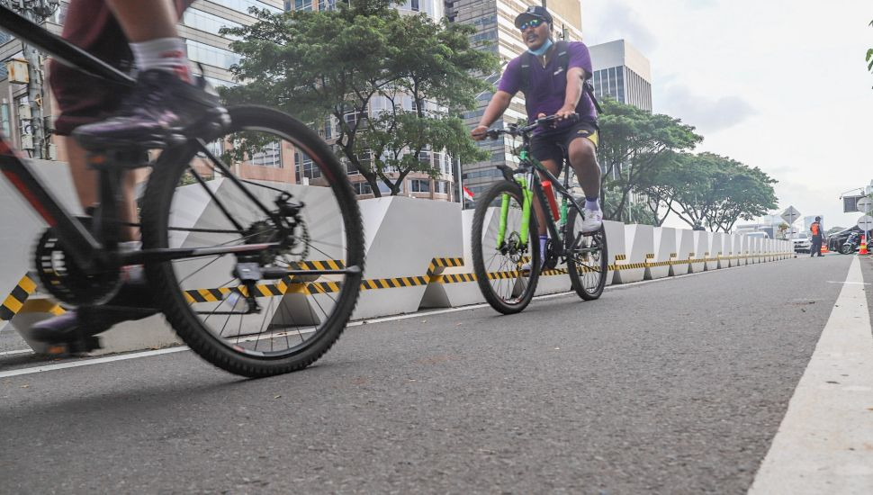 Warga bersepeda menggunakan jalur khusus sepeda di Sudirman, Jakarta Pusat, Jumat (26/2/2021). [Suara.com/Alfian Winanto]